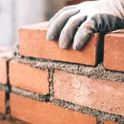 Zement, Ziegelstein und Maurer, zum einer Wand zu bilden